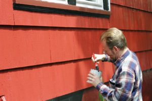 Man holding paint can next to house with red wood siding.