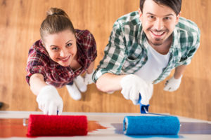 A young man and woman smile while painting a wall red and blue with rollers