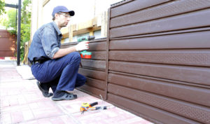 Contractor performs wood vinyl siding installation on house